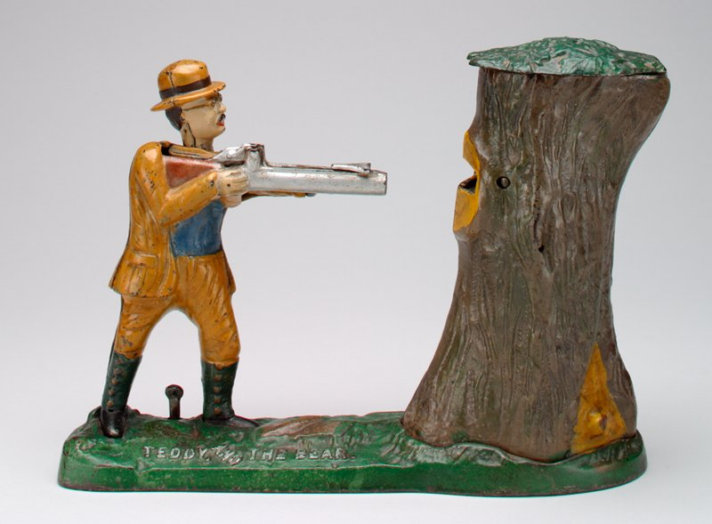 hunter in ochre colored jacket and pants, light blue shirt and black boots, holding silver gun in hands; gun pointed at tree trunk; green lid on tree trunk opens; bear fits inside tree trunk; man wearing glasses