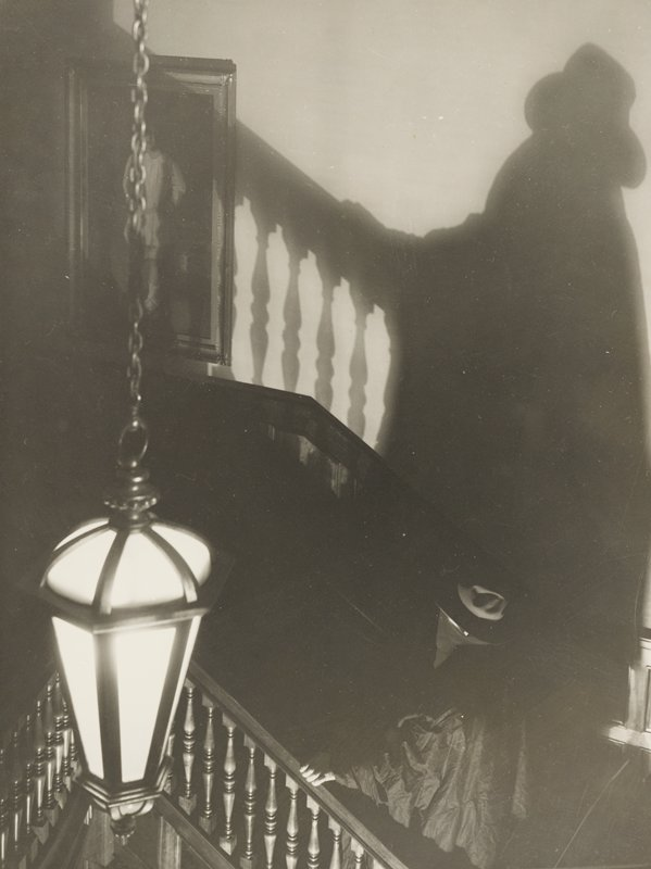 figure in black, with bandana across face and wearing hat, ascending staircase with painting at top; pendant light fixture, LLC; tall shadows at top and R