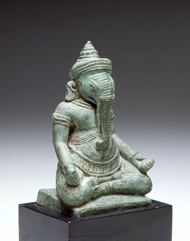 seated figure with male body and elephant's head; wearing a caplike crown; flowerlike element on back of costume