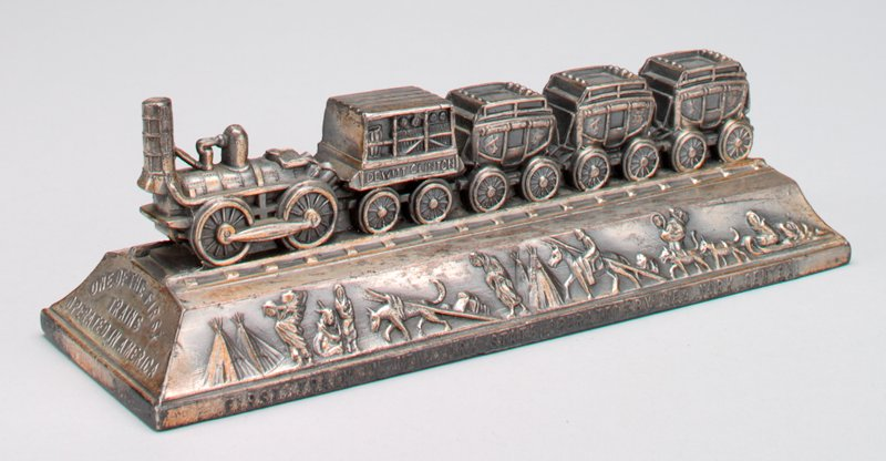train with 3 passenger cars and 1 freight car, on a pedestal; wagons, oxen, horses and train in relief on one side of pedestal; Native Americans and dogsled on opposite side