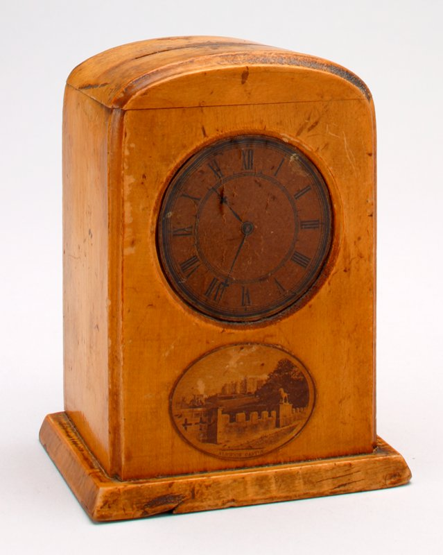 wood mantle clock shape, with paper print of Alnwich Castle below the clock face; clock face is set at 10:34; coin slot at the top; lever at the back to remove coins