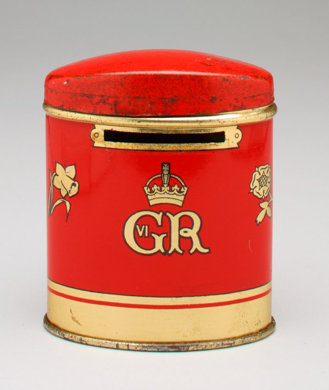 red oval shaped bank with removable lid; coin-like round center in gold with profile of George VI and Elizabeth in black with text in black; gold thistle; 3 shamrocks; daffodil and flower around images; gold initials with gold crown above in back; gold and red bands around bottom