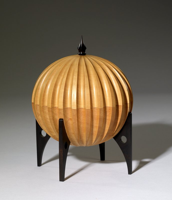 light-colored round vessel with curved vertical flutes; four tapering black legs, each with circular cutout; domed cover with pointed black finial
