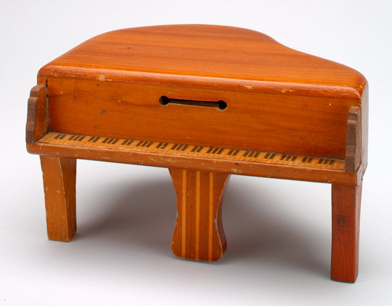 "wooden baby grand piano bank; light brown stain; multicolored pedals; keys printed on paper and applied to wood; coin slot above keys; slot has rounded ""drilled ends""; screw at underside releases wooden slat to open bank"