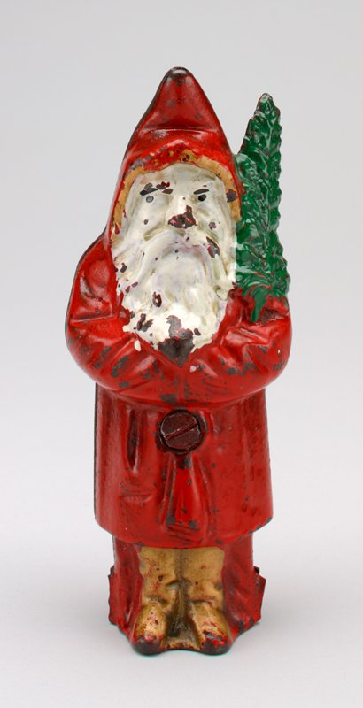 figure of man with white beard wearing red hooded coat trimmed with gold, gold boots and carrying a green branch; coin slot in back