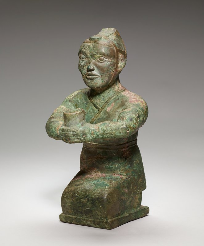 This small sculpture of a kneeling man holding a tube-like vessel in his extended hands is one of a group of similar figures that may have served as torch bearers in a tomb. The sensitively modelled face, with an expression at once tentative and hopeful lends credibility to this supposition. The figure is clothed in a close-fitting garment that wraps from left to right in a broad overlap and is belted with a narrow band. The head-covering, rather like an open helmet, is broad at the back and rises to a peak-like top before descending in a narrow, tounge-shaped band to the forehead. It is bound to the head by a strap that goes down in front of the ears and under the chin. A second strap passes around the head from the forehead to the occiput. This figure is one of a group of bronze sculptures found in the Han family tombs a Kin-ts'un near Lo-yang and reported by W. C. White in Tombs of Old Lo-Yang. The artistic tradition of the early Yin culture, modified by an approach to nature, still persists in some of these small bronze sculptures from the old Lo-yang area. Their general characteristics - the unvarying block-like form, the broad type with large round eyes, the details of costume, particularly the head gear, reflect a new interest in and a closer observation of nature. Such figures constitute the links between early Yin sculptures and those of Han time. Essential characteristics of the earlier works do persist, but in a modified form. One discerns also in these small works, as in some other early Chinese bronzes, a resemblance to certain examples of pre-Columbian art -- a kind of parallelism which points to a similar artistic disposition or a common origin, rather than to any direct influence or intercommunication between these centers of art so widely separated in time and space. However this paralleleism came about, it is clear that the sculptural products of Yin-Chou art reflect traditions of style no longer to be found in those of Han time. Patina green