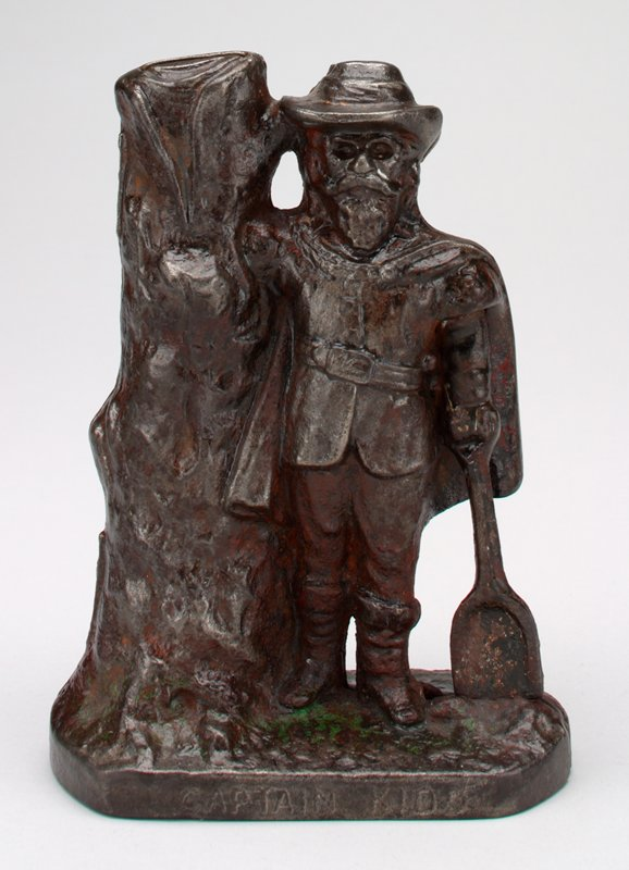 man with tree and shovel; coin slot in top of tree; traces of green pigment on base