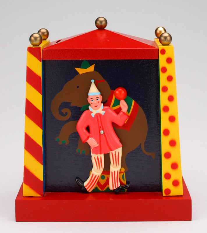 rectangular bank; red and yellow; dancing clown figure; painted elephant behind; weight lifter and accordian player on sides; 5 gold balls on peaked top; coin slot in top