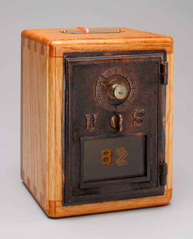 bank made of post office box number 82 with combination lock on front; description of bank in plastic sleeve attached with string; felt pads glued on bottom; combination glued to bottom