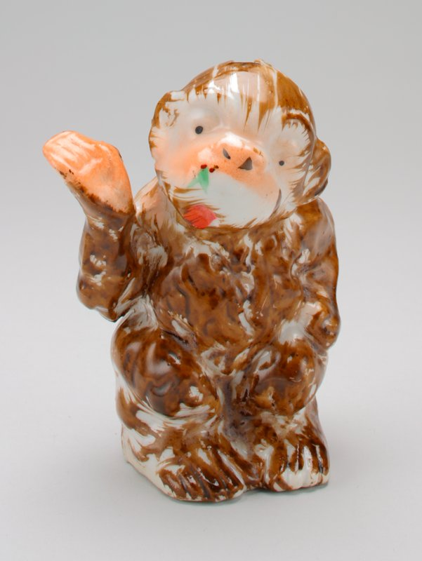 "seated ceramic brown and white monkey; one hand raised; head is tilted and sticking out tongue; 2 leaves and 2 berries painted on nose; ""Made in Japan"", stamped on bottom in red; shiny glaze"