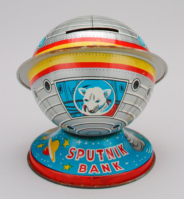 "round metal silver sputnik bank on a blue pedestal with a white dog wearing a space helmet, looking out the window of the capsule; ""Sputnik"" is printed on the base in red with pictures of stars and planets"