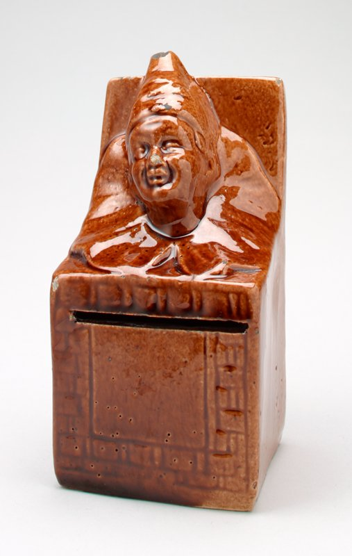 ceramic clown Jack-in-the-Box bank with shiny brown glaze; clown has large round collar and pointed hat; the box cover is open behind the clown; the box front is decorated with incised geometric designs