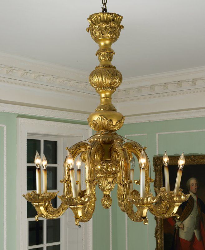 chandelier of carved wood; baluster stem with acanthus carving; the arms are frilled with acanthus leaves and wide candle sockets of graceful shape formed of acanthus leaves