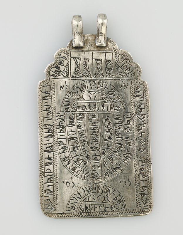 pendant with 2 loops at top; roughly rectangular shape with lobed top; incised decoration (text?) overall on front in linear and arced shapes