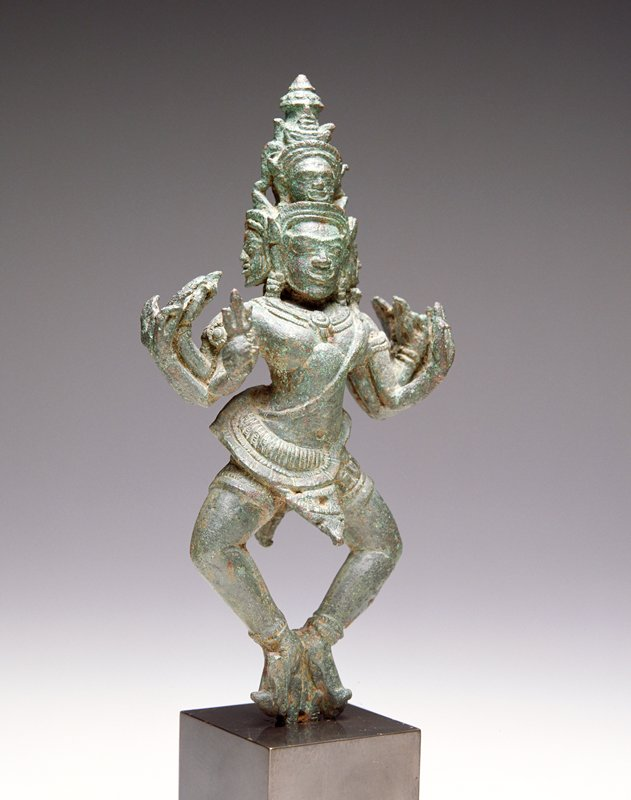dancing figure standing on toes with knees apart; 5 heads and 10 arms; figure has dagger attached to the back of his costume