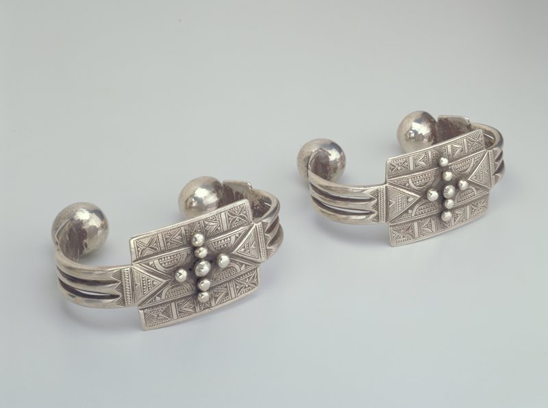 silver cuff bracelet with ball ends; top is flat, decorated with geometric patterns