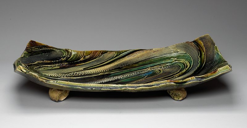 rectangular platter with swirled incised design; green, blue and brown swirled glazes; knob-like feet with felt bottoms