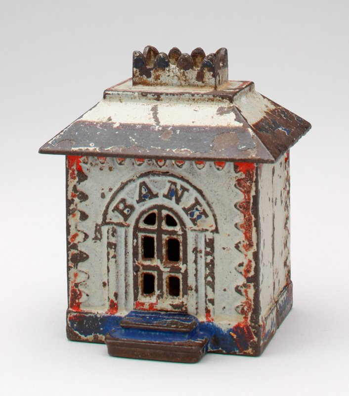 small grey rectangular building; door in front, 2 windows, coin slot and arched alcove in back; red paint below roof, blue around base