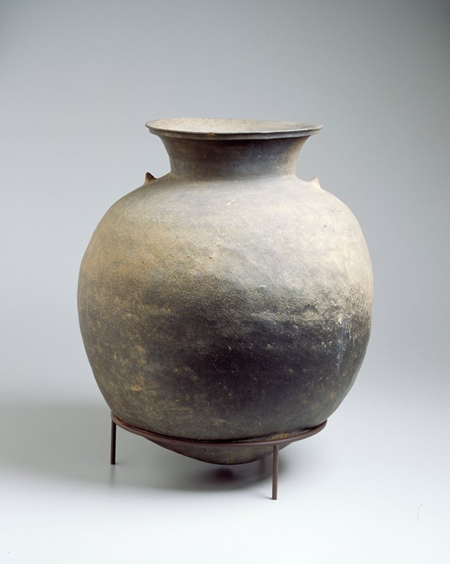 large round grey storage jar, pointed foot, two nipples above shoulders opposite each other, flaired mouth with distinct rim, unadorned; has own stand