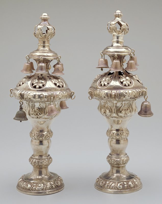 floral repouse design in 4 horizontal bands; openwork floral design at largest point; 2 rows of bells; crownlike openwork finial