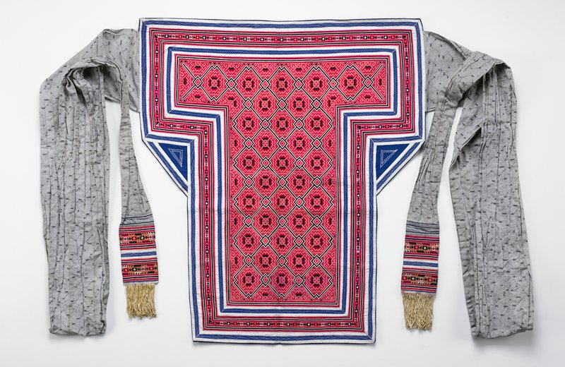 blue backing; black and white printed ties with cream fringe and embroidered and batik end panels; body embroidered in salmon, rose, white and black geometric pattern; blue and white applique border