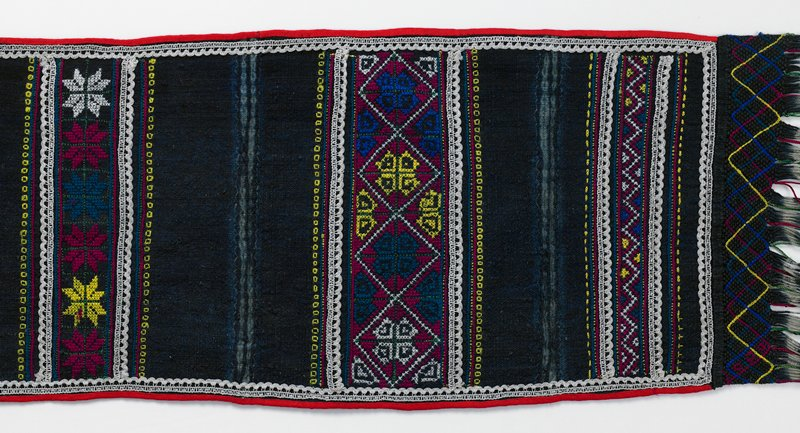 wide sash; indigo dyed with stripes and zigzags; long fringes; 3 bands of geometric and star cross-stitched embroidery at each end; rickrack and lace embelishments at ends