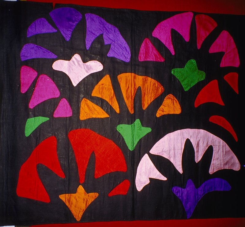 Separate handsewn appliqued pieces make up fan shaped motifs (Black background with multi bright applique designs)