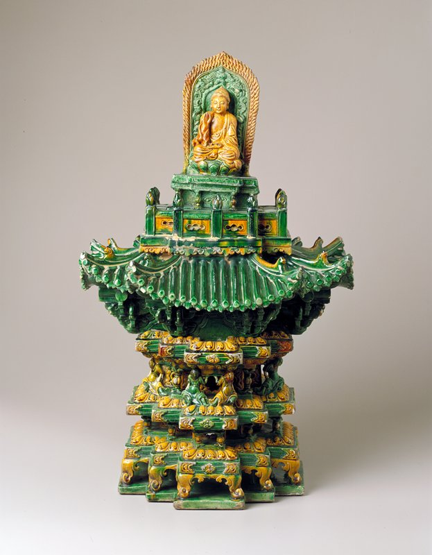 two section pagoda; lower section, elaborate tiers of cruciform section with seated figures supporting the four top most projections; upper section, tiled roof flaring outward beneath a balustrade and a plinth on which a figure of Buddha is seated atop a lotus