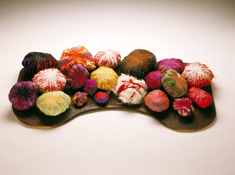 balls of thread on a board a)Purple, magenta, orange, and green yarns wrapped in black thread H.3 x Dia.5-1/2 in; b)Green net wrapped in orange and yelow thread; H.2-1/4 x Dia.5-1/4 in. c)Paper, blue fabric tape wrapped in bright orange thread; H.3-1/2 x Dia.6-1/2 in. d)Burgundy fabric, ocher yarn wrapped in maroon and violet thread; H.2 x Dia.5 in. e)Olive and teal yarn wrapped in brown thread; H. 2-1/2 x Dia.6-3/4 in f)Lavendar and maroon fabric wrapped in navy thread; H.2-1/2 x Dia.5-3/4 in g)cerise fabric werpped in red and purple thread; H.2-3/8 x Dia. 3-3/4 in h)blue fabric and orange net wrapped in red and peach thread; H.2 x Dia.4 in i)hunks of white thread wrapped in orange yarn; H.2-1/4 x Dia.5-1/2 in j)plaid fabric wrapped in orange, purple and maroon thread; H.1-3/4 x Dia.4 in. k)white fabric and maroon ribbon wrapped in purple and maroon thread; H.1-1/2 x Dia.3 in. l)orange fibers wrapped in light blue thread; H.1-3/4 x Dia.5 in. m)orange thread and fabric wrapped in purple thread and purple ribbon; H.1 x Dia.2-5/8 in n)pink, green fibers wrapped in purple thread; H.7-8 x Dia.2-1/4 in o)blue fabric wrapped in orange thread; H.1 x Dia.2-1/4 in p)orange and green yarn wrapped in white thread; H.2-1/4 x Dia.5 in q)light green yarn wrapped in yellow thread; H.2-1/4 x Dia.5 in r)magenta and natural yarn wrapped in white thread; H.2-1/2 x Dia.5 in s)green, yellow and brown yarn wrapped in yellow thread; H.2 x Dia.4-1/2 in t)orange and white wrapped thread; H.2-1/8 x Dia.5-1/2 in u)table top for display; H.1/4 x W.30-1/2 x D.15-1/4 in