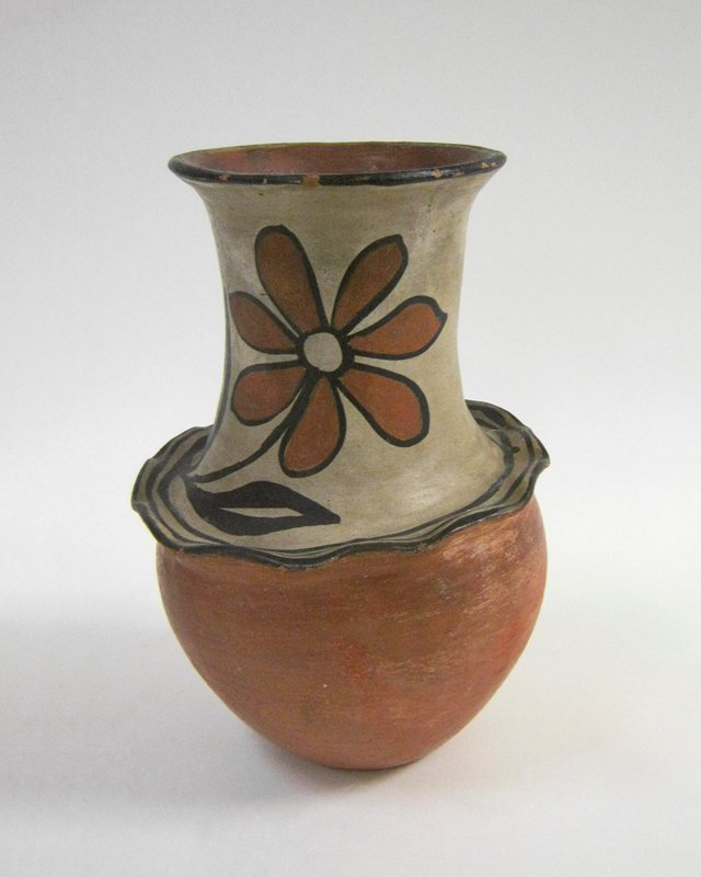 slightly asymmetrical design; rounded bottom with protruding, scalloped shoulder; tall, wide neck with outward-flaring mouth; decorated with 2 large red and black daisies on cream on neck; black and cream mouth; red body