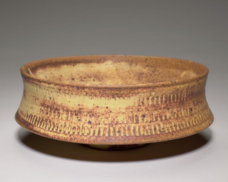 stoneware bowl with added apron from rim covering body of bowl; tall and very small foot; brown and tan glaze; three rows of impressed design at outer apron