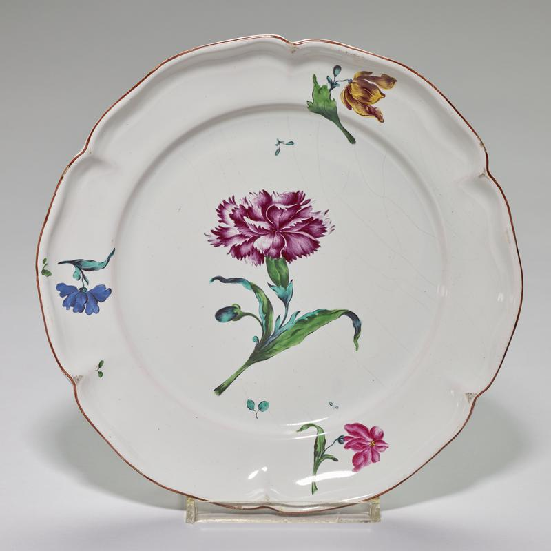 faience plate; rather deep, hexagonal-lobed shape; brown glaze on edge; center contains one large carnation painted in deep red-purple; leaves of carnation highlighted in pale coppery blue and shaded in dark green
