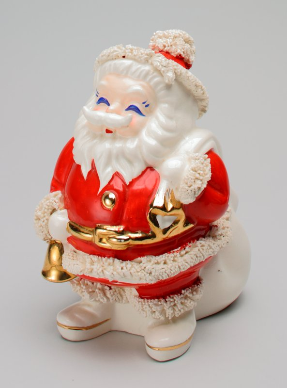 standing Santa Claus figure with gold belt, gold button and gold bell in PR hand; very large, lumpy white sack over PL shoulder; small extruded ceramic tubes at cuffs, hems of coat and pants, hat tassel and bottom edge of hat