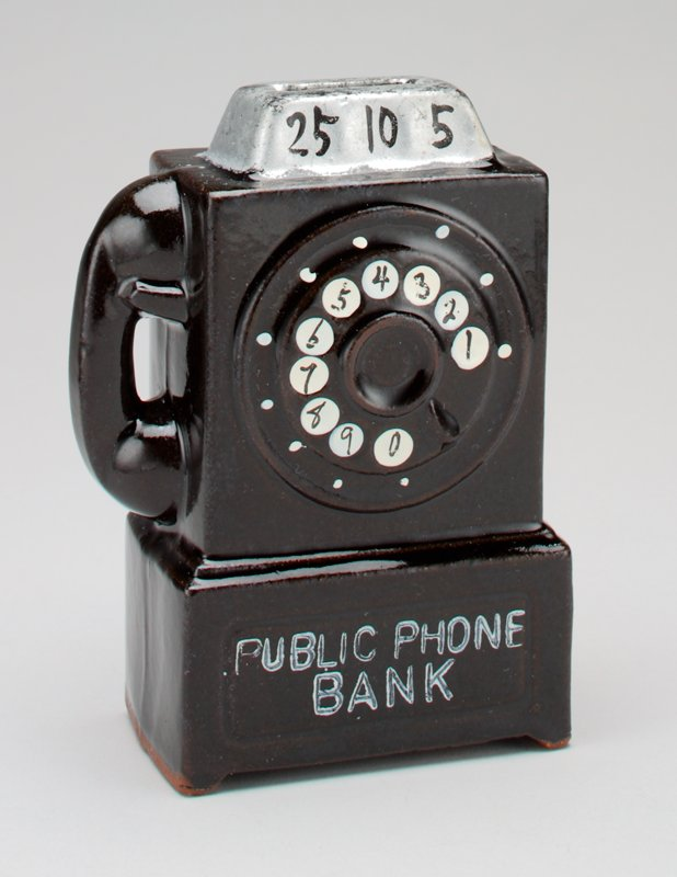 "ceramic bank in the form of a black wall mounted public rotary dial telephone; raised coin slot on top labeled ""25, 10, 5""."