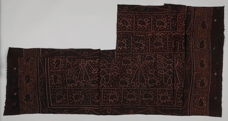 rectangular with extra strip of fabric on one short side; brown with resist tie-dyed spotted pattern including tailed quadrupeds, skirted figures and flowers