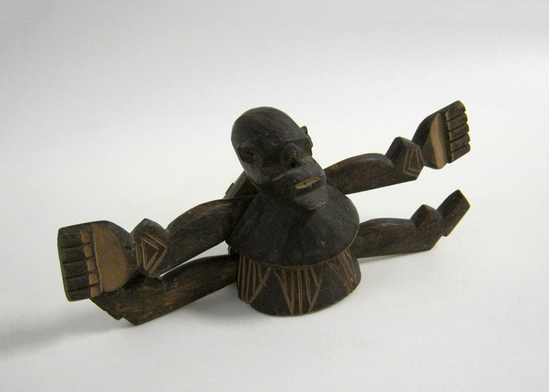 bichrome puppet with straight arms and legs, incised decoration on torso and hands, arms and legs move when central string between legs is pulled