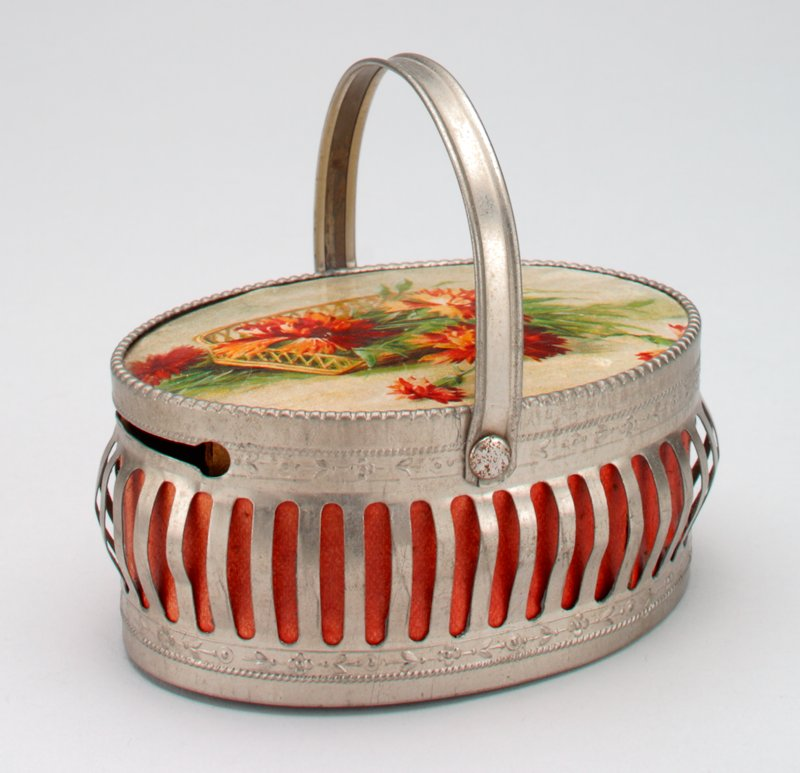 oval metal basket with handle; openwork sides; painting of folwers in and around a basket on top; coin slot in rim of basket;
