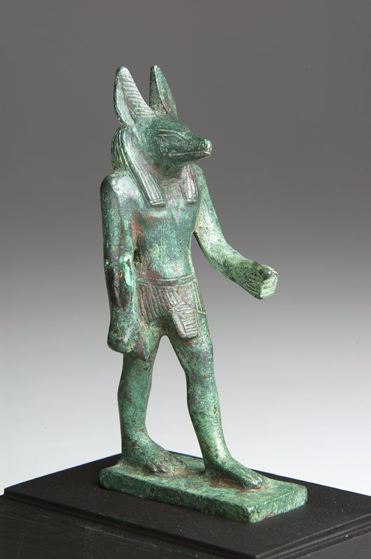 jackal-headed god Anubis, bronze, Egyptian, XVII Dynasty; green patina; eyes, mouth, fingers, toes, hair of ears, strands of wig, vertical folds of short kilt, horizontal folds of the kilt-pendant, all rendered by incised lines; solid casting; body heavy and solid but head rather expressive