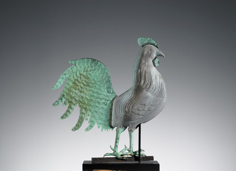 "abstracted rooster; rounded body with delineated wings; flat cut-out head and tail with ""buttons"" at ends of tail feathers; vertical rod through center of body extending into decorative base; black patina"