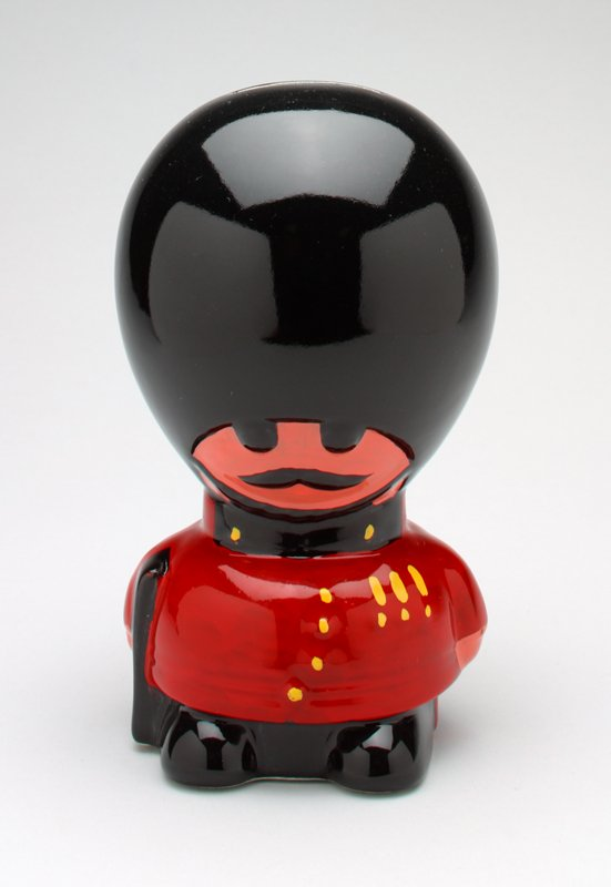 """caricature of a British beefeater in ceramic with black hat with chinstrap; black pants, shoes and gun, red jacket with yellow decoration, pink face and hands, black eyes and moustache; plastic cover on bottom with """"Made in England"""""""