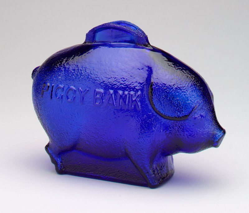 blue glass standing pig; floppy ears; on each side of pig, printed in raised letters: 'Piggy Bank'; raised coin slot on back of pig