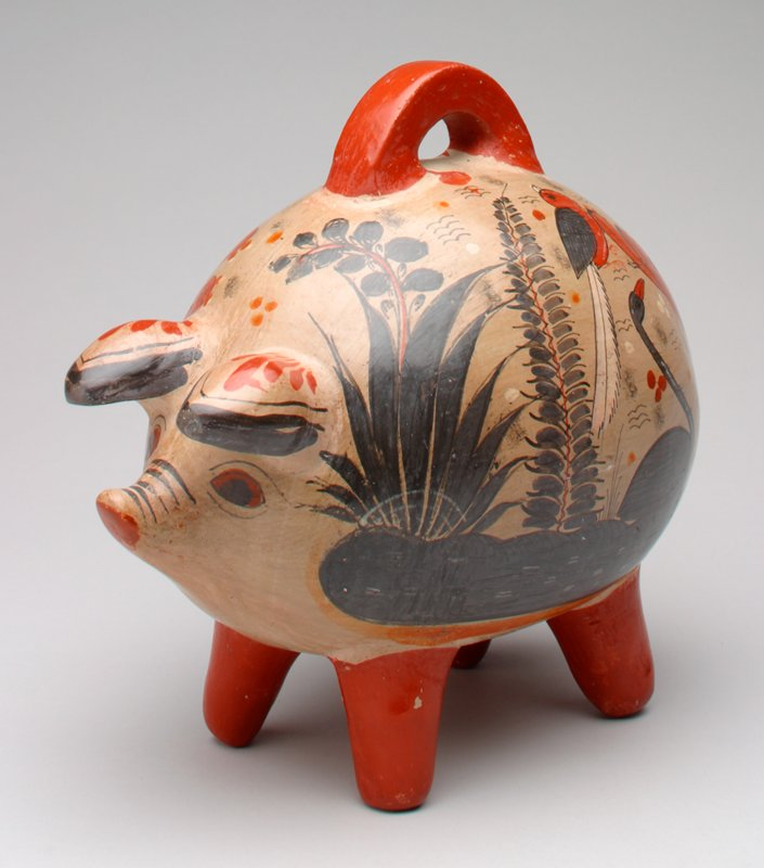 tan pig painted with dark green plants, rust cactus and animals; rust legs and handle; coin slot below handle proper right;