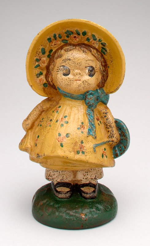 cast iron girl wearing a yellow dress and sunbonnet; with pantaloons, parasol and black shoes; bank in 2 sections held together by a screw; on a green base