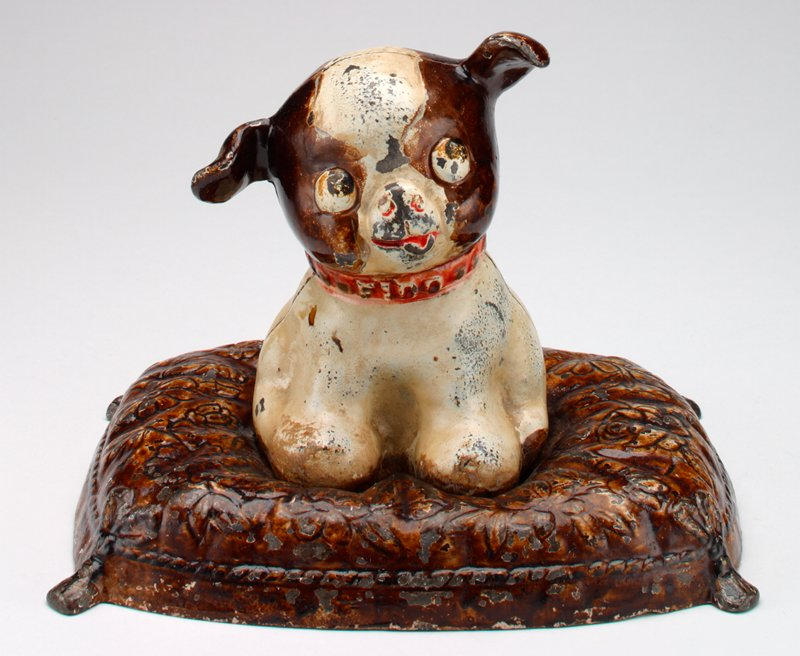 seated dog, white with brown spots, seated on a brown floral cushion; red collar; coin slot in back of neck