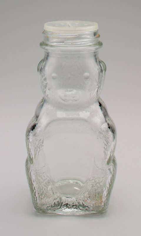clear glass seated bear with plastic cap; cap has 6 holes and a coin slot