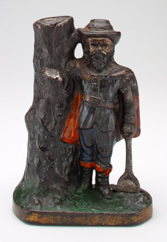 """standing figure of a man wearing a cape, boots, and hat, holding a shovel, leaning on a tree trunk; coin slot on top of tree trunk; on front of base is printed: """"CAPTAIN KIDD"""""""