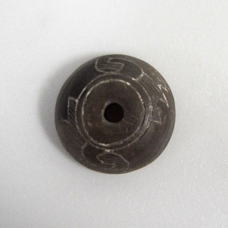 One in a group of seven spindle whorls, having incised designs, some on top, bottom and sides, others on top and sides ceramic. .5 (199/5) L.3/4, Diam. 1-7/8 in.