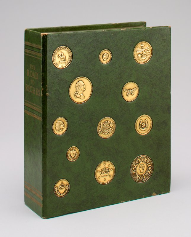 """book shape covered in imitation green leather with gold coins on one side; the spine of the book is titled """"The Road to Riches""""; a coin slot in the top of the book; a metal cover at the bottom of the book"""