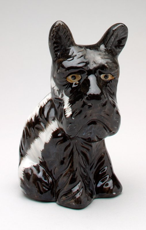 black ceramic sad-eyed Scottie dog with white stripes on back and cheeks; shiny glaze; the dog is in a seated position looking down; coin slot at back of head