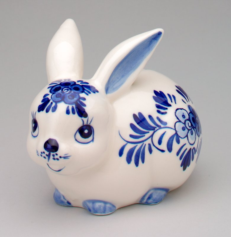 Delft rabbit with blue feet and nose; floral designs on sides and forehead; coin slot on back and rubber stopper on bottom